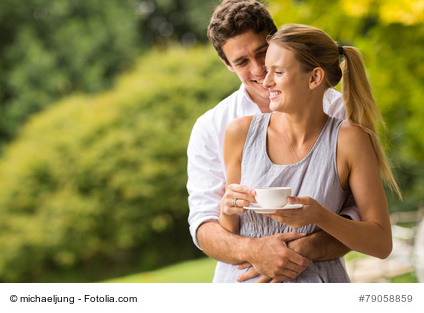 happy young man hugging wife outdoors