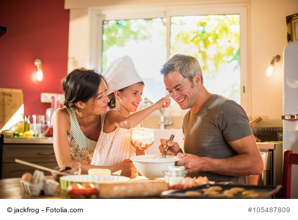 7 years old girl with chef hat is having fun with parents