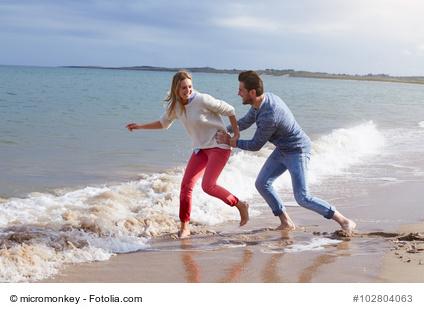 Couple On Beach Vacation Running In Sea
