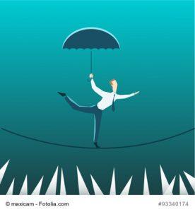 Businessman with an umbrella over the precipice
